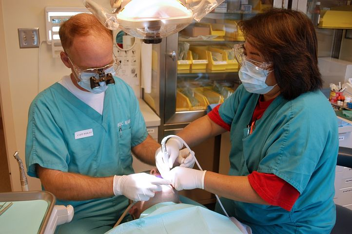 two dentists checking a patient's mouth